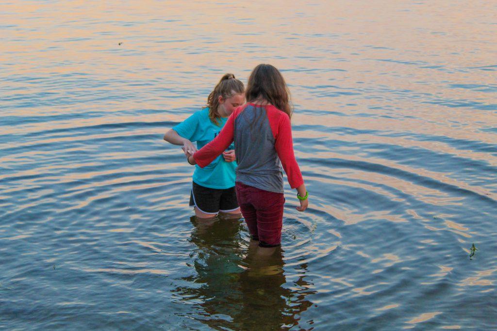 Girls wadding into lake