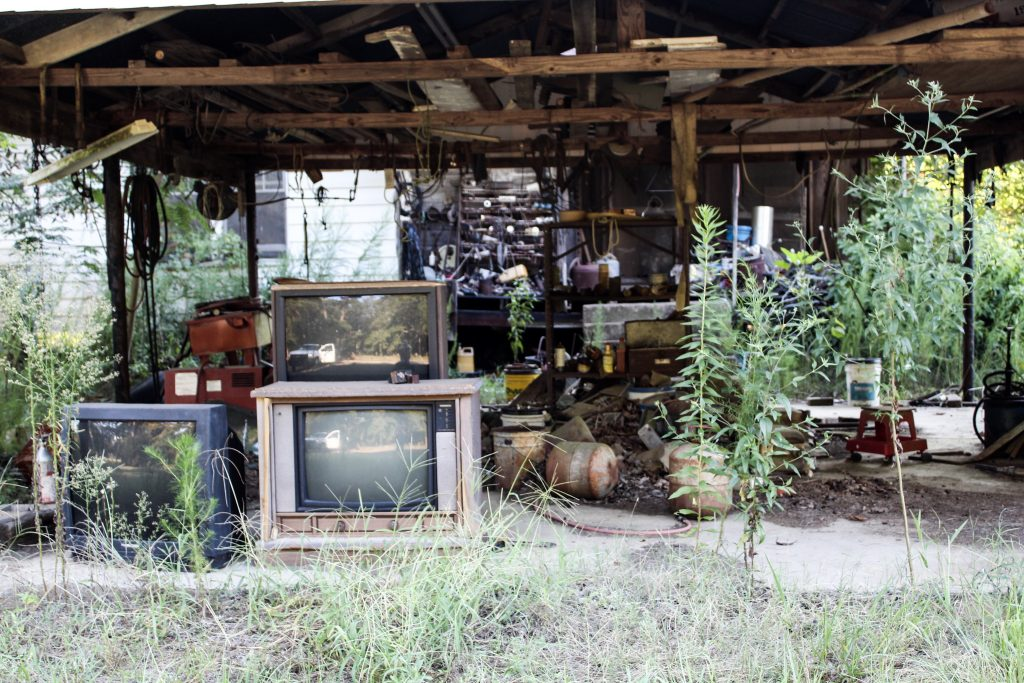 Old tube tvs under a carport