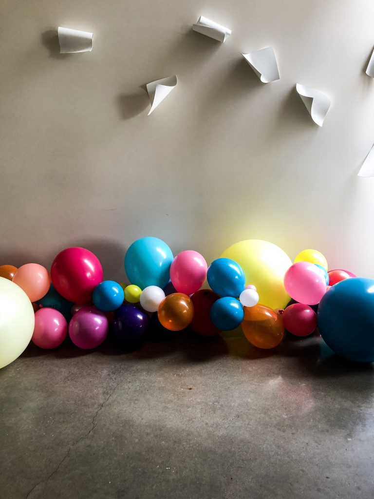 Colorful balloons sitting on the floor. Paper art exhibit above.
